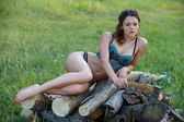 Sexy girl on the pile of firewood — Stock Photo