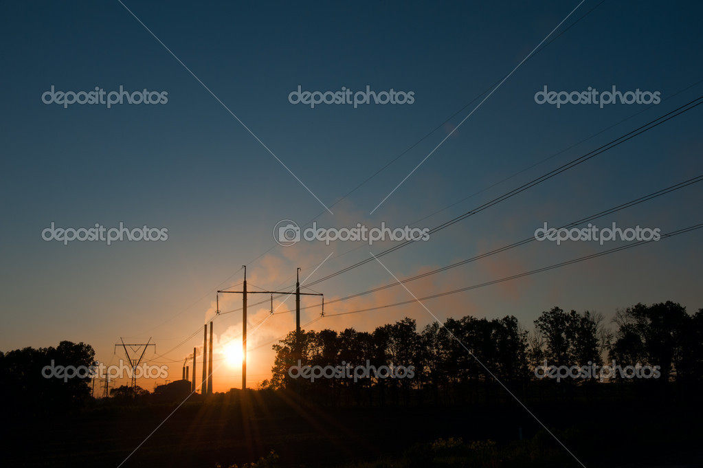 Wonderful landscape of lines of electricity transmissions and smoking industrial pipes on a gold sunset background — Stock Photo #5402586
