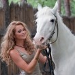 Rural pretty girl with a stallion — Stock Photo