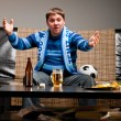 Soccer fan on sofa - Stockfoto