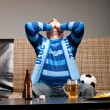Stock Photo: Soccer fan on sofa