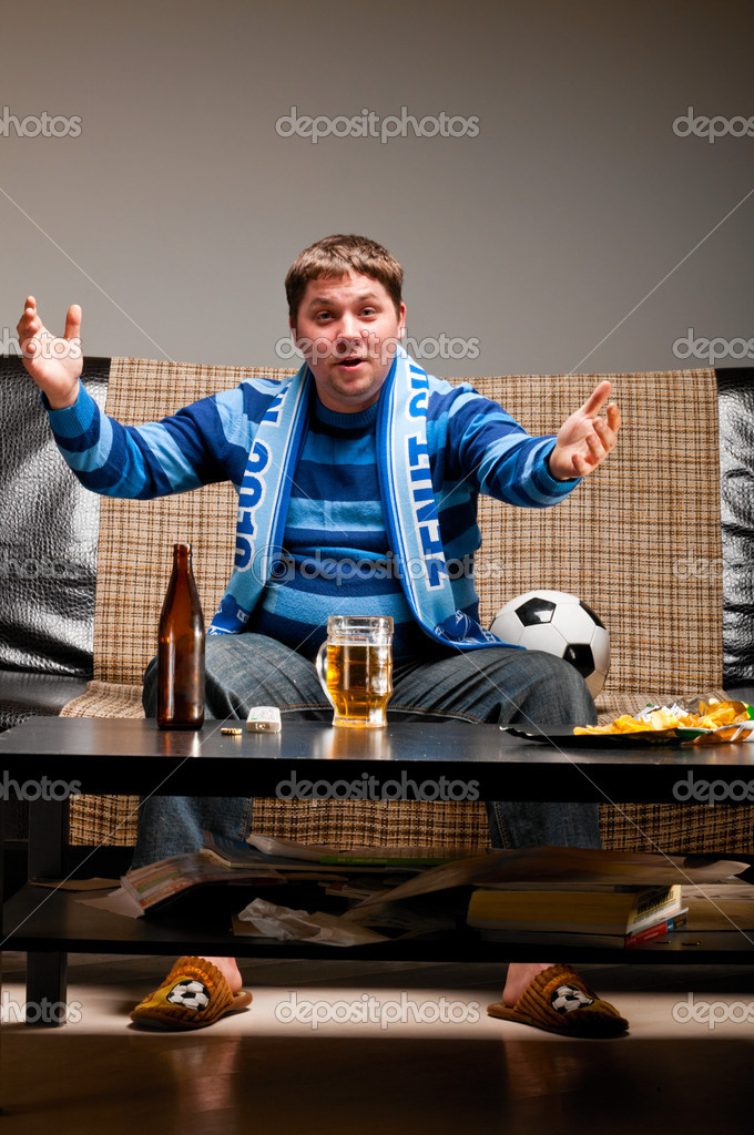 Soccer fan is sitting on sofa with beer at home and applauding — Stock Photo #5451204