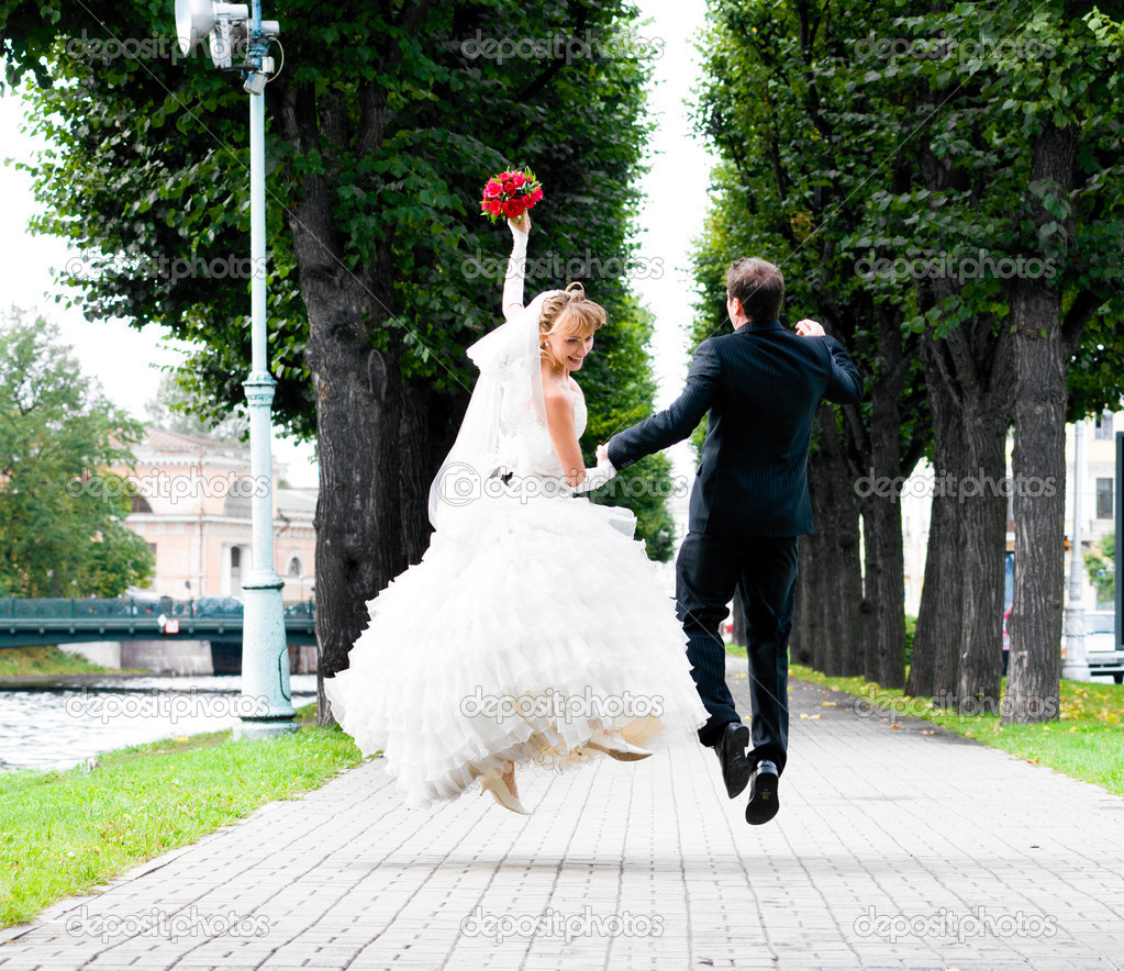 Bride and groom is running with joined hands on city park road — Stock Photo #5473041