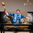 Soccer fan on sofa - Photo