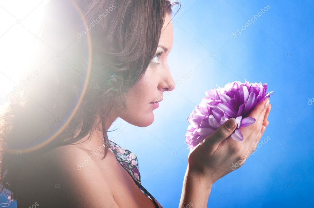 Beautiful woman with big flower on blue background — Stock Photo #5644428