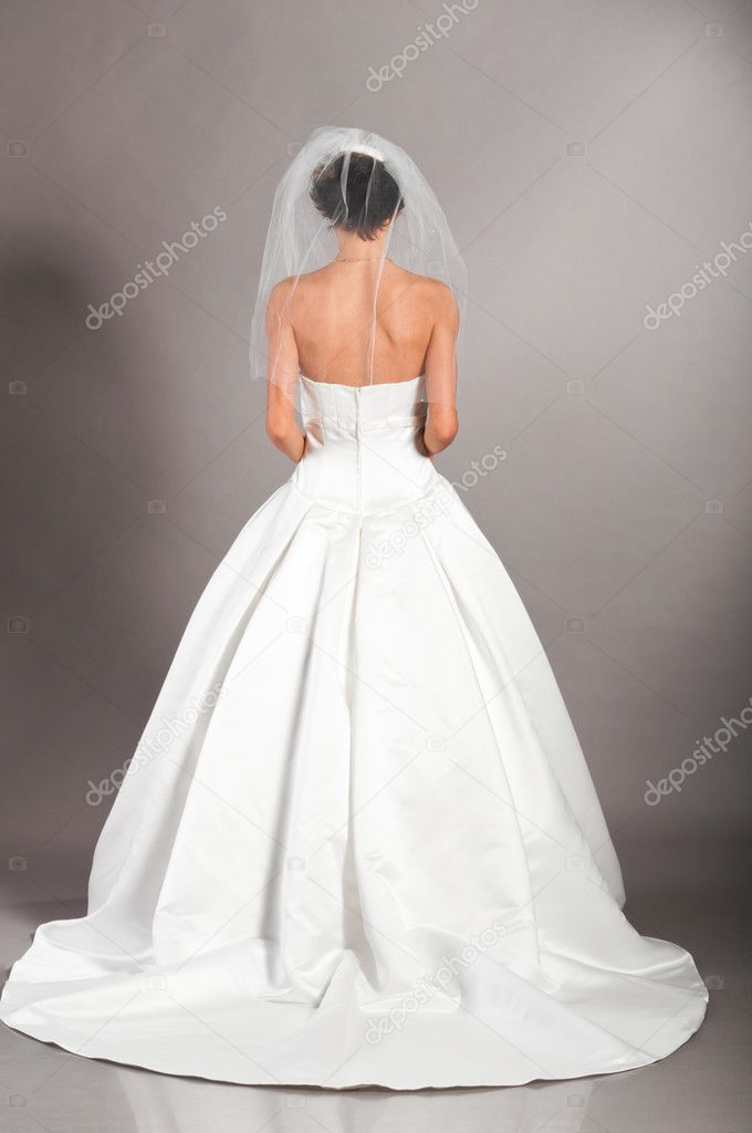Beautiful bride is standing in wedding dress on grey background, view from behind — Stock Photo #5661880