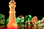 Red and green glass chess pieces — Stock Photo