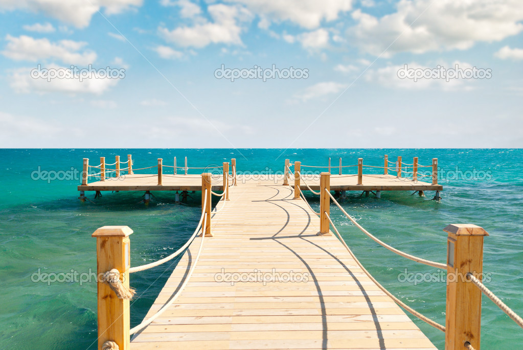 Tropical wooden pier in turquoise sea at sunny weather, cloudy skies — Stock Photo #5971318