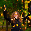 Throwing dry autumn leaves in park — Stock Photo #6088179