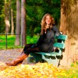 Sitting on the bench in autumn park — Stock Photo