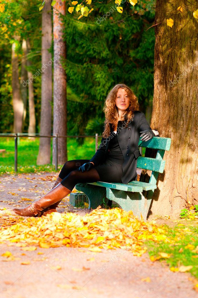 Young woman is sitting on the bench in autumn park and looking at camera  Stock Photo #6088299