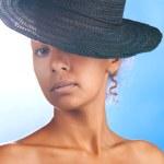 Mulatto woman wearing black straw — Stock Photo