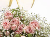 Two glasses with champagne and bouquet roses — Stock Photo