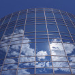 Windows of skyscraper with reflections against blue sky — Stock Photo
