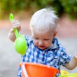 Toddler playing in sand - Stock Photo