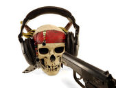 Skull in ear-phones with the weapon — Stock Photo