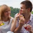 Young happy couple eating together outdoors — Stock Photo