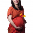 Adult pregnant woman with flowers — Stock Photo