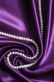 White pearls on a lilac silk — Stock Photo
