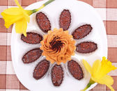 Cake and chocolates on the white plate with yellow daffodils — Stock Photo