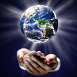 Stock Photo: Man holding a glowing earth globe in his hands