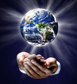 Man holding a glowing earth globe in his hands — Stock Photo