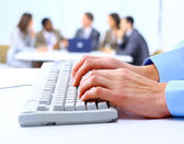 Image of male hands typing on keyboard in a working environment — Stock Photo