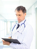 Happy smiling mature doctor writing on clipboard in a modern hospital — Stock Photo