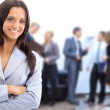 Successful business woman standing with her staff in background at office — Stock Photo #5497609