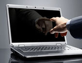 Close-up of male hand with forefinger pointing at laptop screen over black — Stock Photo