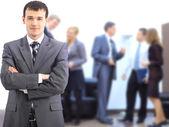 деловой человек в офисе с группой за ним — Стоковое фото