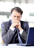 Thoughtful businessman looking at his laptop — Stock Photo
