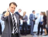Framgångsrik verksamhet man står med sin stab i bakgrunden på kontor — Stockfoto