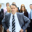 Business man at the office with a group behind him — Stock Photo