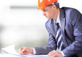 Site manager in the office with blue helmet — Stock Photo