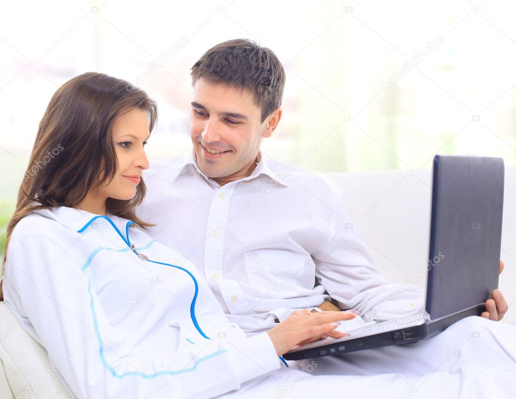 Portrait of a happy young couple sitting on a sofa using laptop  — Stock Photo #5563314