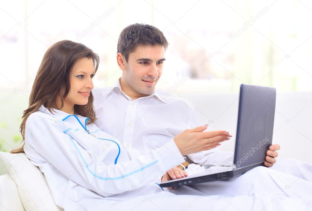 Portrait of a happy young couple sitting on a sofa using laptop   Stock Photo #5563322