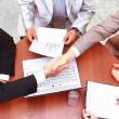 Stock Photo: Handshake over paper and pen,blurry computer in background