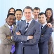 Group of co-workers standing in office space smiling — Stock Photo