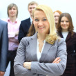Beautiful blond businesswoman in front of her team — Stock Photo