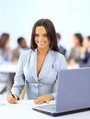 在办公室工作的年轻快乐微笑女商人 — 图库照片