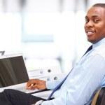 retrato de um empresário americano africano feliz exibindo computador lapto — Foto Stock
