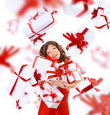 Excited attractive woman with many gift boxes and bags. — Стоковое фото