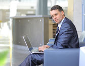 Casual looking businessman working on laptop computer in front of office wi — Stock Photo