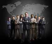 Businessmen standing in front of an earth map — Stock Photo