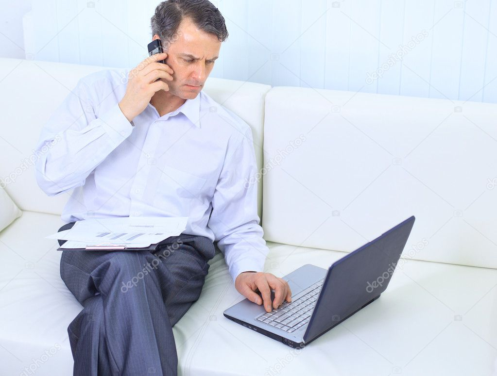 Entrepreneur working from home looking very relaxed in his sofa browsing the web in his laptop computer  — Stock Photo #5658346