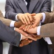 Group of business making a pile of hands in a light and modern offic — Stock Photo #5706028