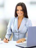 Young happy smiling businesswoman working at office — Stock fotografie
