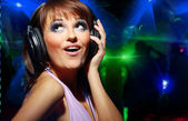 Radiant young woman listen to music wearing headphones — Stock Photo