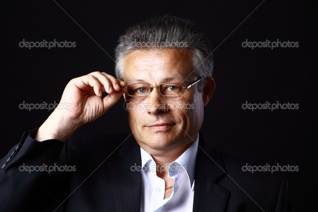 Portrait of successful business man standing on black background  — Stock Photo #6004192